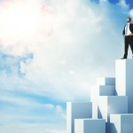 Businessman standing on highest cube